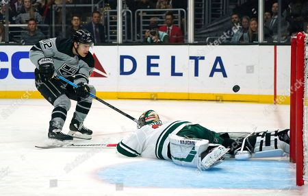 Los Angeles Kings center Trevor Moore, left, scores on Minnesota Wild goaltender Alex Stalock during the second period of an NHL hockey game, in Los Angeles