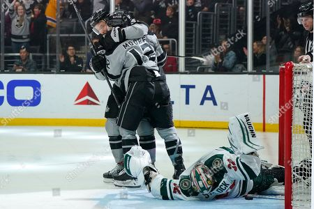 Los Angeles Kings center Trevor Lewis, left, congratulates center Trevor Moore, center, after Moore scored on Minnesota Wild goaltender Alex Stalock during the second period of an NHL hockey game, in Los Angeles