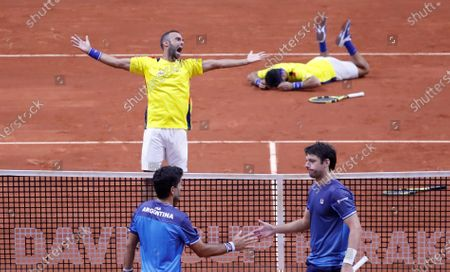 Stock Image of Colombian tennis players Juan Sebastian Cabal (L-top) and Robert Farah (R-top) celebrate after beating the Argentinian team Maximo Gonzalez (L-bottom) and Horacio Zeballos (R-bottom), after a match in the qualifying phase of the Davis Cup 2020 between Colombia and Argentina, at the Palacio de los Deportes (Sports Palace) in Bogota, Colombia, 07 March 2020.