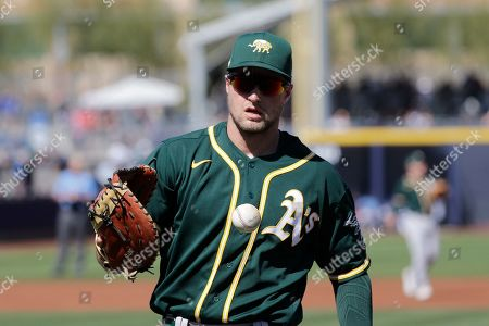 Stock Picture of Oakland Athletics first baseman Seth Brown pops the ball from his mitt during a spring training baseball game, in Peoria, Ariz