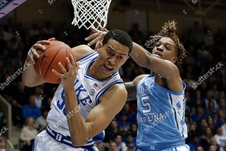 Duke forward Justin Robinson grabs a rebound while North Carolina forward Armando Bacot (5) defends during the first half of an NCAA college basketball game in Durham, N.C