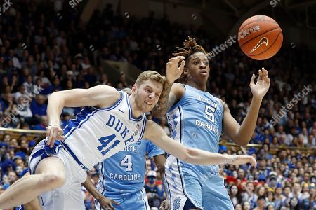 Duke forward Jack White (41) and North Carolina forward Armando Bacot (5) struggle for a rebound during the first half of an NCAA college basketball game in Durham, N.C