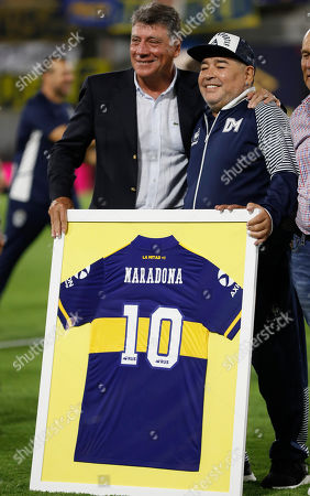 Gimnasia y Esgrima's coach Diego Maradona, right, poses with formers soccer player Miguel Brindici prior to an Argentina's soccer league match against Boca Juniors at La Bombonera stadium in Buenos Aires, Argentina