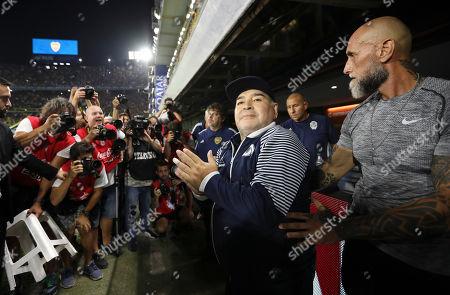Gimnasia y Esgrima's coach Diego Maradona applauds prior to an Argentina's soccer league match against Boca Juniors at La Bombonera stadium in Buenos Aires, Argentina