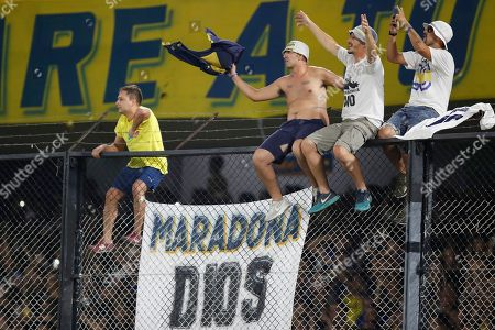 """Fans of Boca Juniors cheer next to a banner reading in Spanish """"Maradona God"""" during an homage to former soccer star Diego Maradona prior to an Argentina's soccer league match between Boca Juniors and Gimnasia y Esgrima at La Bombonera stadium in Buenos Aires, Argentina,. Maradona, currently Gimnasia y Esgrima's coach, played twice for Boca Juniors during his career"""