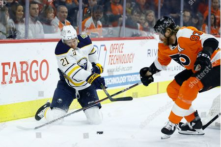 Buffalo Sabres' Kyle Okposo (21) passes the puck against Philadelphia Flyers' Jakub Voracek (93) during the first period of an NHL hockey game, in Philadelphia