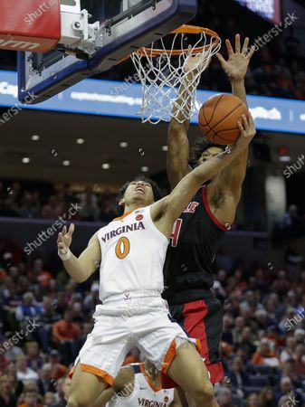 Virginia Cavaliers Guard (0) Kihei Clark is fouled on his way to the hoop by Louisville Cardinals Guard (4) Grant Williams during a NCAA Men's Basketball game between the Louisville Cardinals and the University of Virginia Cavaliers at John Paul Jones Arena in Charlottesville, VA