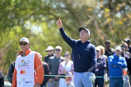 Davis Love III, right, tests the wind direction before hitting his tee shot on the seventh hole during the third round of the Arnold Palmer Invitational golf tournament, in Orlando, Fla