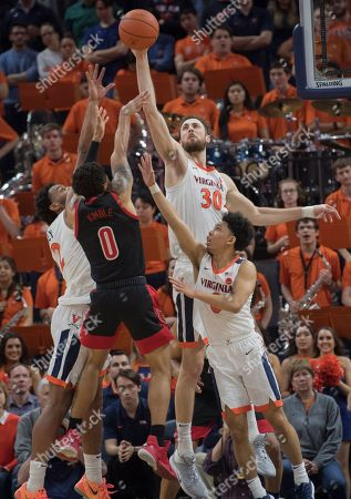 Virginia forward Jay Huff (30) blocks a shot by Louisville's Lamarr Kimble during the second half of an NCAA college basketball game in Charlottesville, Va