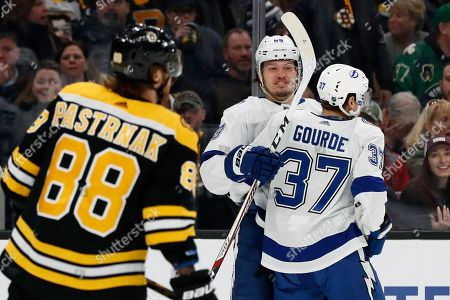 Stock Image of Tampa Bay Lightning's Mikhail Sergachev celebrates his shorthanded goal with teammate Yanni Gourde (37) as Boston Bruins' David Pastrnak skates away during the first period of an NHL hockey game, in Boston