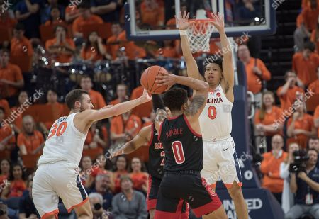 Virginia defender Kihei Clark (0) leaps as teammate Jay Huff (30 blocks shot by Louisville guard Lamar Kimble (0) during the second half of an NCAA college basketball game in Charlottesville, Va