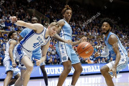 Duke forward Jack White (41) chases a rebound with North Carolina forward Armando Bacot (5) and guard Leaky Black, right, during the first half of an NCAA college basketball game in Durham, N.C