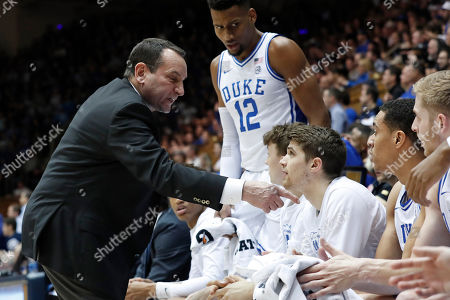 Duke head coach Mike Krzyzewski speaks to his players during the first half of an NCAA college basketball game against North Carolina in Durham, N.C