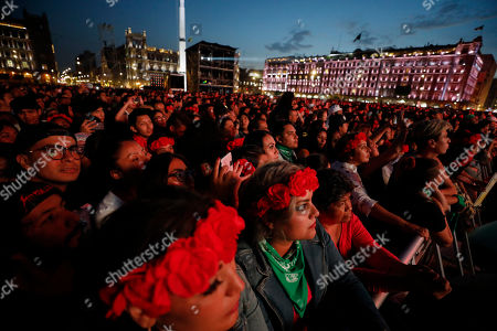Spectators look on as French-Chilean singer Ana Tijoux performs during a concert by female artists on the eve of International Women's Day, in the Zocalo in Mexico City,. Protests against gender violence in Mexico have intensified in recent years amid an increase in killings of women and girls, and women are expected to express their outrage in a march in Mexico City on Sunday