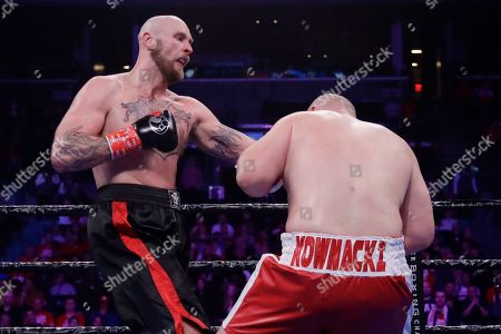 Sweden's Robert Helenius, left, knocks down Poland's Adam Kownacki during the fourth round of a heavyweight boxing match, in New York. Helenius stopped Kownacki in the fourth round