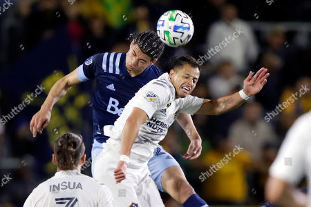 Vancouver Whitecaps defender Jasser Khmiri, left, battles LA Galaxy forward Javier Hernandez, right, for a header during the first half of an MLS soccer match in Carson, Calif