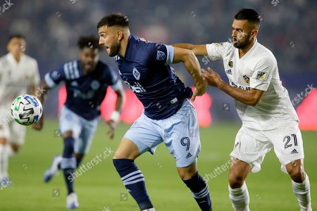 Vancouver Whitecaps forward Lucas Cavallini, left, battles LA Galaxy defender Giancarlo Gonzalez, right, to get to the ball during the first half of an MLS soccer match in Carson, Calif