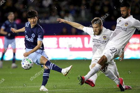 LA Galaxy defender Giancarlo Gonzalez, right, deflects a shot by Vancouver Whitecaps midfielder Hwang In-beom, left, with forward Aleksandar Katai also defending during the first half of an MLS soccer match in Carson, Calif