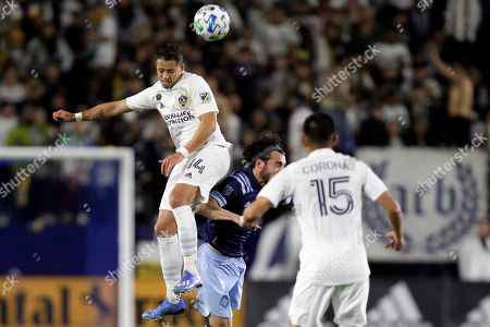 LA Galaxy forward Javier Hernandez, left, heads the ball away from Vancouver Whitecaps midfielder Russell Teibert, center, with midfielder Joe Corona, right, watching during the first half of an MLS soccer match in Carson, Calif