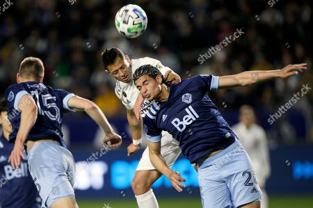 LA Galaxy forward Javier Hernandez, center, tries to head the ball between Vancouver Whitecaps defender Jasser Khmiri, right, and midfielder Andy Rose during the second half of an MLS soccer match in Carson, Calif