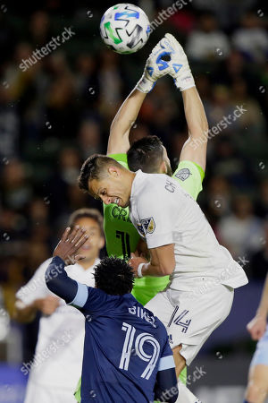 Vancouver Whitecaps goalkeeper Maxime Crepeau, above, loses the ball after LA Galaxy forward Javier Hernandez, center, bumped into the goalie, with Whitecaps midfielder Janio Bikel, below left, defending during the second half of an MLS soccer match in Carson, Calif