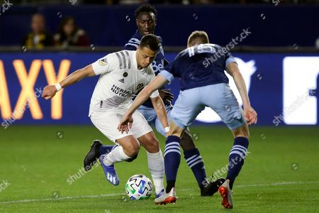 Los Angeles Galaxy forward Javier Hernandez, center, controls the ball between Vancouver Whitecaps midfielder Andy Rose, right, and midfielder Janio Bikel during the second half of an MLS soccer match in Carson, Calif