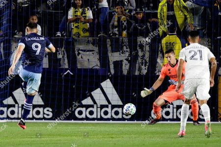 LA Galaxy goalkeeper David Bingham, center, stops a penalty shot by Vancouver Whitecaps forward Lucas Cavallini, left, with defender Giancarlo Gonzalez, right, watching during the second half of an MLS soccer match in Carson, Calif