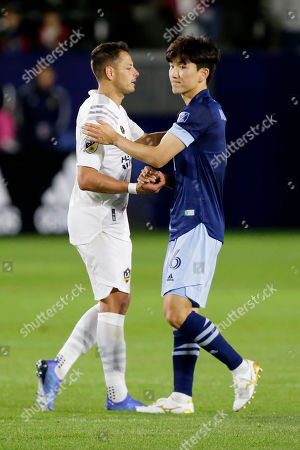 LA Galaxy forward Javier Hernandez, left, congratulates Vancouver Whitecaps midfielder Hwang In-beom after the Whitecaps defeat the LA Galaxy 1-0 in an MLS soccer match in Carson, Calif