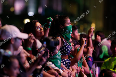 Spectators, some wearing green bandanas like those worn in recent women's protests, look on as French-Chilean singer Ana Tijoux performs during a concert by female artists on the eve of International Women's Day, in the Zocalo in Mexico City,. Protests against gender violence in Mexico have intensified in recent years amid an increase in killings of women and girls, and women are expected to express their outrage in a march in Mexico City on Sunday