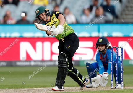 Australia's Alyssa Healy, left, drives the ball in front of IndiaÅfs Tanya Bhatia during the WomenÅfs T20 World Cup cricket final match against India in Melbourne
