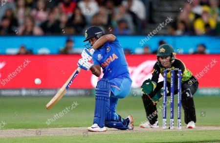 India's Harmanpreet Kaur, left, plays a shot in front of Australia's Alyssa Healy during the Women's T20 World Cup cricket final match in Melbourne