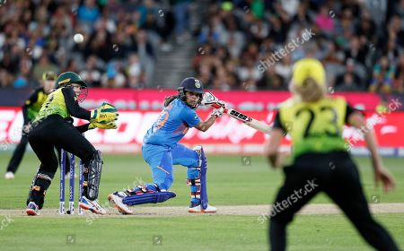 India's Veda Krishnamurthy, center, plays a shot past Australia's Alyssa Healy, left, during the Women's T20 World Cup cricket final match in Melbourne