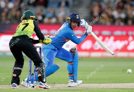 India's Richa Ghosh, right, plays a shot past Australia's Alyssa Healy during the Women's T20 World Cup cricket final match in Melbourne