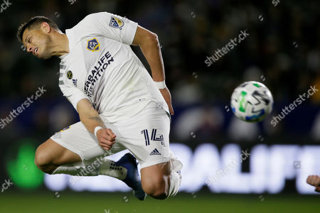 LA Galaxy forward Javier Hernandez heads the ball behind him during the second half of an MLS soccer match against the Vancouver Whitecaps in Carson, Calif