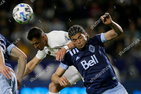 LA Galaxy forward Javier Hernandez, left, battles Vancouver Whitecaps defender Jasser Khmiri, right, for the ball during the second half of an MLS soccer match in Carson, Calif