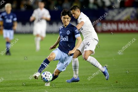 Vancouver Whitecaps midfielder Hwang In-Beom, left, controls the ball away from LA Galaxy forward Javier Hernandez, right, during the second half of an MLS soccer match in Carson, Calif