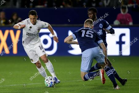 Stock Image of LA Galaxy forward Javier Hernandez, left, controls the ball against Vancouver Whitecaps midfielder Andy Rose, center, and midfielder Janio Bikel, right, during the second half of an MLS soccer match in Carson, Calif