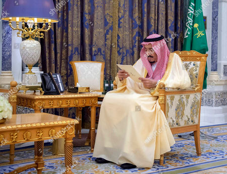 Saudi King Salman reads a document as he receives two newly appointed Saudi ambassadors at his palace in Riyadh, Saudi Arabia, . Two senior princes in Saudi Arabia are under arrest for not supporting Crown Prince Mohammed bin Salman, who has consolidated control of all major levers of power with the support of his father, King Salman, two people close to the royal family said Saturday