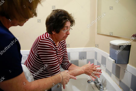 Maria Casal Hernandez, Maria Castro. Maria Casal Hernandez, RN., left, helps Maria Castro wash her hands at Little Havana Activities and Nutrition Centers of Dade County, Inc., in Miami. The new coronavirus is posing a special challenge for nursing homes and other facilities that provide care for the elderly