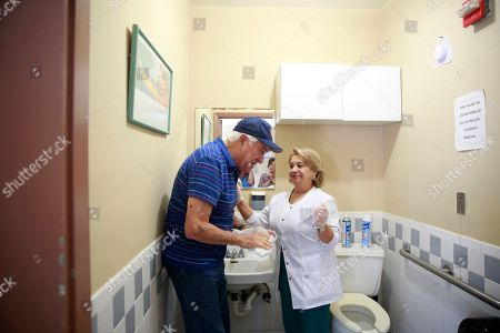 Maria Castro, Rene Gonzalez. Nursing assistant Natasha Borges, right, helps Rene Gonzalez, left, dry his hands after washing them at Little Havana Activities and Nutrition Centers of Dade County, Inc., in Miami. The new coronavirus is posing a special challenge for nursing homes and other facilities that provide care for the elderly