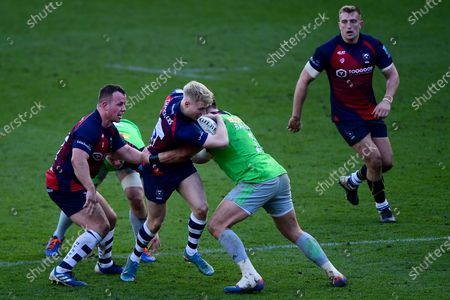Mat Protheroe of Bristol Bears is tackled by Scott Baldwin of Harlequins
