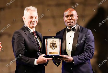 Stock Image of Egyptian actor Mahmoud Hemeida (L) hands Haitian actor Jimmy Jean-Louis (R) an honorary trophy at the opening ceremony of Luxor African Film Festival (LAFF), Luxor, Egypt, 06 March 2020 (issued 08 March 2020). The festival will continue till 12 March 2020. The festival celebrates African cinema. LAFF opening ceremony took place in Luxor temple and was presented by actress Sanaa Youssef and TV presenter Mona Salman.