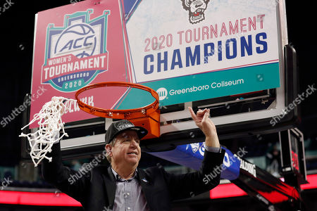 North Carolina State head coach Wes Moore holds the net after his team defeated Florida State in an NCAA college basketball championship game at the Atlantic Coast Conference women's tournament in Greensboro, N.C