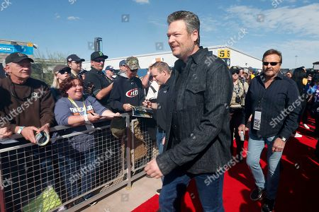Country music singer and television personality Blake Shelton, center, walks past race fans prior to a NASCAR Cup Series auto race at Phoenix Raceway, in Avondale, Ariz