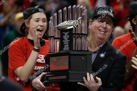North Carolina State head coach Wes Moore holds the championship trophy following an NCAA college basketball championship game against Florida State at the Atlantic Coast Conference women's tournament in Greensboro, N.C