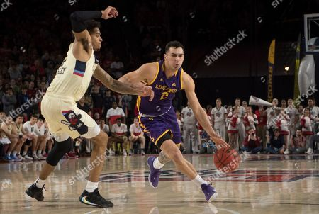 Lipscomb guard Andrew Fleming drives around Liberty defender Caleb Homesley during the second half of the Atlantic Sun Conference NCAA basketball championship game in Lynchburg, Va