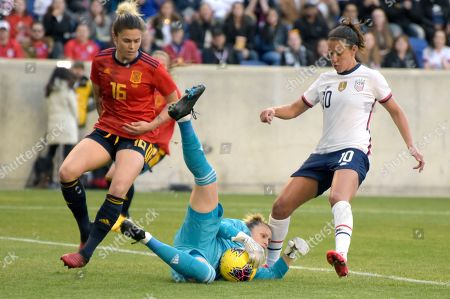 Spain goalkeeper Sandra Paños (13) makes a save as United States forward Carli Lloyd (10) closes in during the first half of a SheBelieves Cup soccer match, in Harrison, N.J