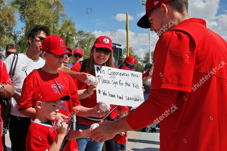 Taylor Cole, Nash Theriault, Kaden Theriault, Jeannine Theriault. Los Angeles Angels relief pitcher Taylor Cole, right, hands a baseball back to Nash Theriault, left, as his brother Kaden Theriault waits for an autograph and his mother, Jeannine Theriault, center, stands holding a sign about the coronavirus before a spring training baseball game, in Phoenix, Ariz