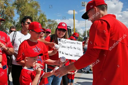 Stock Photo of Los Angeles Angels relief pitcher Taylor Cole, right, hands a ball back to Nash Theriault, left, as his brother Kaden Theriault waits for an autograph and his mother, Jeannine Theriault, center, stands holding a sign about the coronavirus before a spring training baseball game, in Phoenix, Ariz