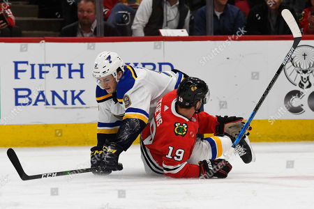 St. Louis Blues left wing Sammy Blais (9) and Chicago Blackhawks center Jonathan Toews (19) get wrapped up during the first period of an NHL hockey game between the Chicago Blackhawks and the St. Louis Blues, in Chicago